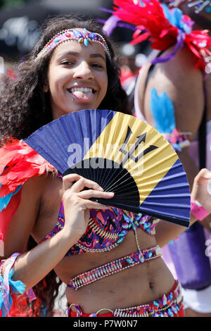 Montreal, Canada. 7/7/2018.A young woman with a fan participates in the  Carifiesta parade in downtown Montreal. Credit: richard prudhomme/Alamy Live News - Stock Image