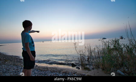 Kid playing at the beach during sunset - Stock Image
