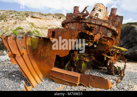 Close up stern view of pusher boat wrecked at the beach amidst cliffs. The wreckage has many years and the boat - Stock Image