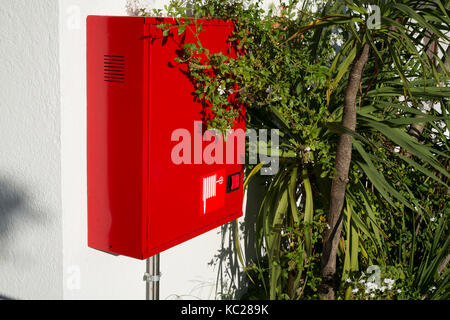 Red fire hose against green shrubbery in Lloret de Mar, Spain - Stock Image