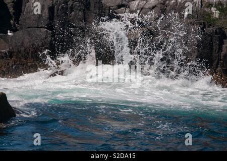 Waves crashing on sea stacks - Stock Image