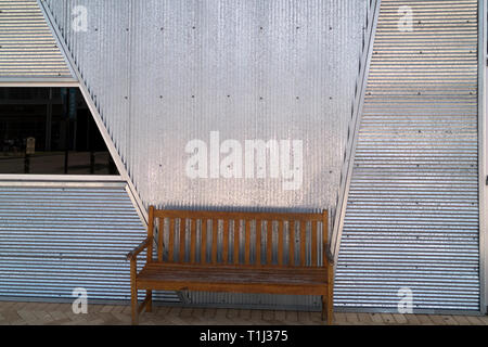 Park bench sitting outside a retail business at The Wharf in Orange Beach, Alabama. - Stock Image