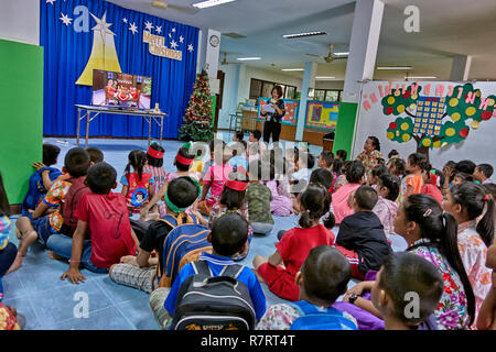 Thailand Christmas.  School teacher explaining Xmas and showing a movie to a classroom of young children - Stock Image
