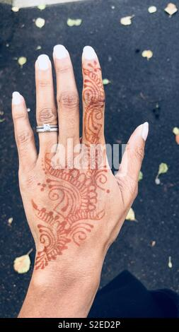 An Indian female hand with mehndi or henna on her hand - Stock Image