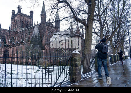 Chester, Cheshire, UK. 30th December 2018. Two people photograph a snow covered Chester Cathedral from the city walls. Credit: Andrew Paterson/Alamy Live News - Stock Image