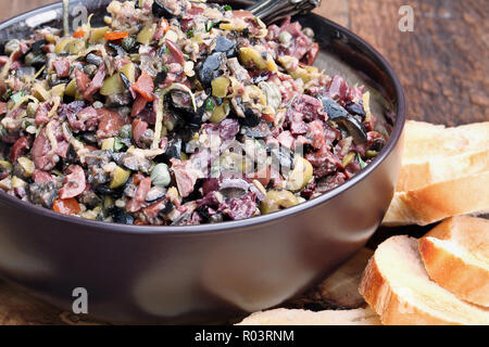Homemade mixed Olive Tapenade made with garlic, capers, olive oil, Kalamata, black and green olives with toasted bread. Extreme shallow depth of field - Stock Image