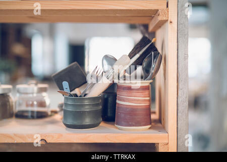 Close-up of cutleries with paintbrushes in containers on shelf at workshop - Stock Image