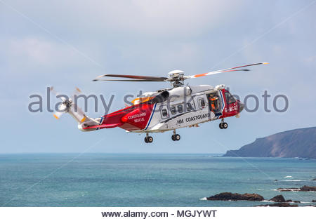 A Sikorsky S92 search and rescue helicopter of the Maritime and Coastguard Agency flies on practice manoeuvres with the RNLI at Bude, North Cornwall - Stock Image