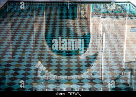 Arch reflected on pool, Ali ben Youssef Medersa (Koranic school), Marrakech, Morocco - Stock Image