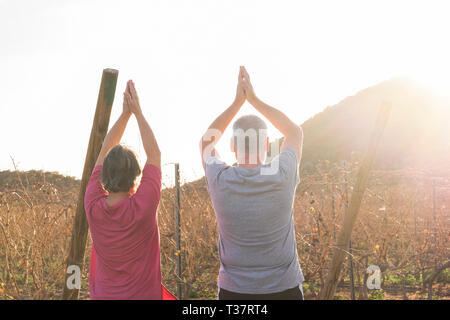 Happy active couple of old senior cacuasian people man and woman do yoga position for healthy lifestyle outdoor leisure activity - sunlight in backlig - Stock Image