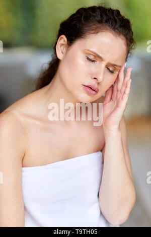 Woman sat with a headache - Stock Image