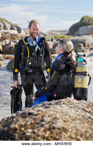 Couple in wetsuits going ocean scuba diving from rocky beach - Stock Image