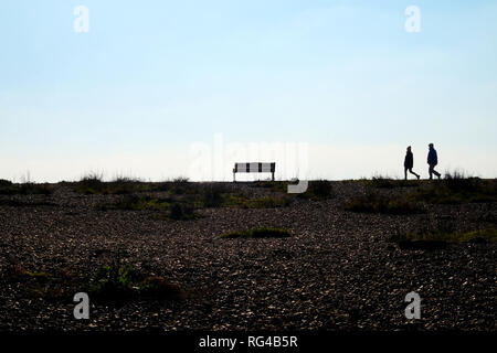 In the foreground is a pebble beach at the end of the beach are two unrecognizable people walking together as a couple they are siluoetted by the sun  - Stock Image