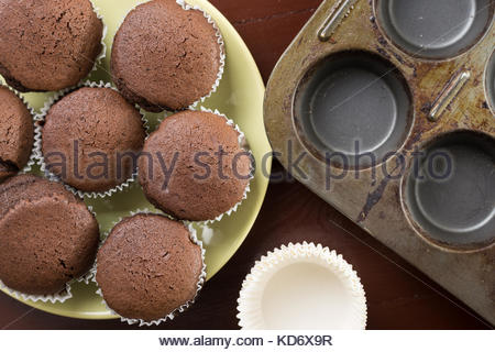 Flat lay above fresh baked chocolate cup cakes on the plate with baking tray in the background. - Stock Image