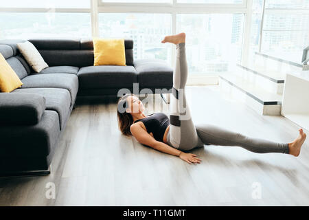 Fit young Pacific Islander woman training at home. Beautiful female athlete working out for wellbeing in domestic gym, training her abdomen. She lays  - Stock Image