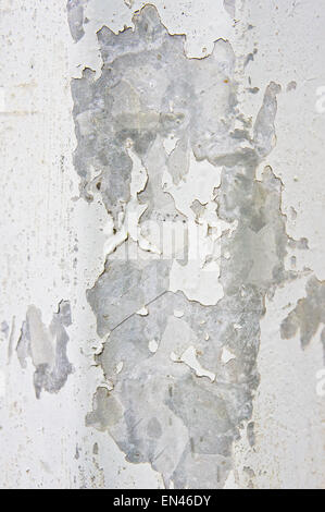 Peeling white paint on a metallic surface as a background image - Stock Image