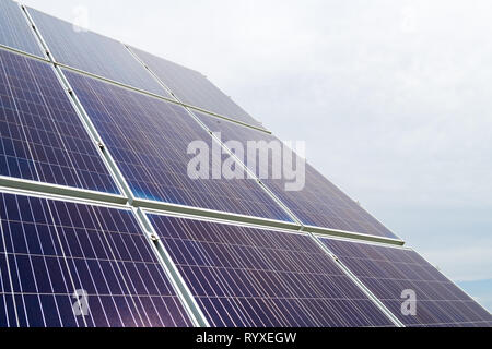 Solar cell photovoltaic panels at energy production plant with blue cloudy sky in the background. Solar renewable energy concept - Stock Image