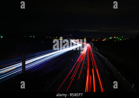 Car trails at night along a road and a city on the background - Stock Image