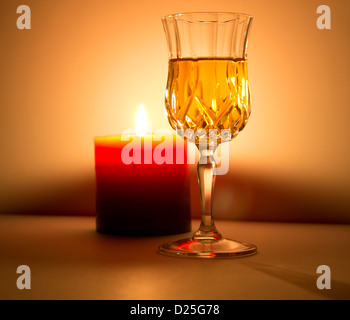 A candle gives light to a fine liquor. - Stock Image