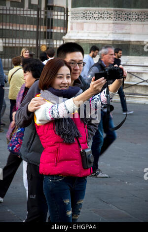Tourists taking 'selfie' photo in front of Cathedral & Campanile, Piazza del Duomo, Florence, Tuscany, - Stock Image