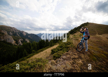 Cyclist drinking water while standing on mountain with bicycle - Stock Image