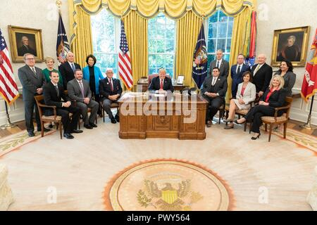 """U.S President Donald Trump, joined by Vice President Mike Pence and members of his Cabinet pose for a group photo after the """"Cutting the Red Tape and Unleashing Economic Freedom"""" event in the Oval Office of the White House October 17, 2018 in Washington, DC. - Stock Image"""