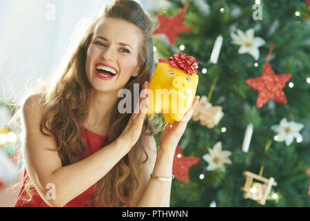 happy trendy woman in red dress shaking yellow piggy bank with red bow near Christmas tree - Stock Image