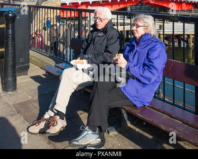 Man and a woman eating a snack and enjoying the autumn sunshine on a seat by Whitby Harbour bridge North Yorkshire - Stock Image
