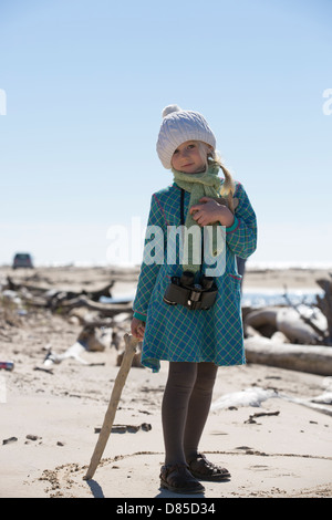Small girl on a beach with binoculars around her neck, portrait - Stock Image