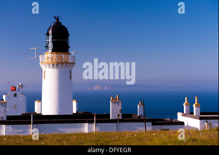 dunnet head lighthouse with old man of hoy across water in mist - Stock Image