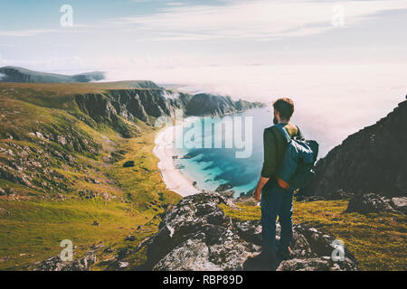 Summer travel man tourist standing alone on mountain top over ocean beach active lifestyle hiking adventure vacations in Norway outdoor - Stock Image