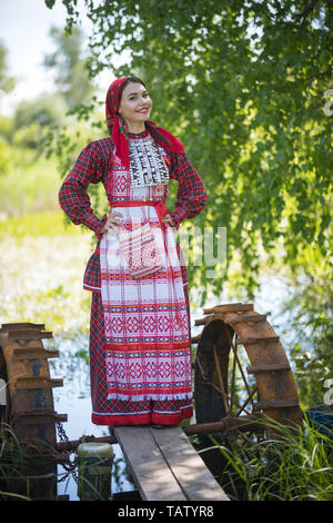 Young woman in scarf and traditional russian clothes stands on a small pier near the lake and holds hands on a waist looking left vertical view. - Stock Image