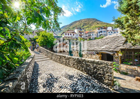 Tourists walk a narrow cobblestone path over a bridge and past a cafe in the medieval city of Mostar, Bosnia on an autumn morning. - Stock Image