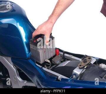 Motorcycle, removing battery, keeping it upright to avoid spillage. - Stock Image