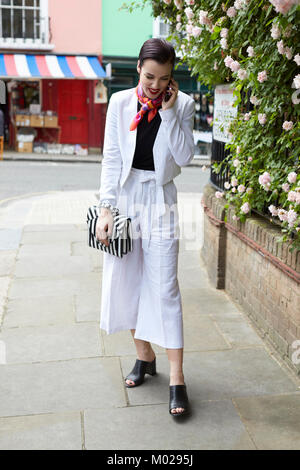Woman in white linen suit using phone in street, full length - Stock Image