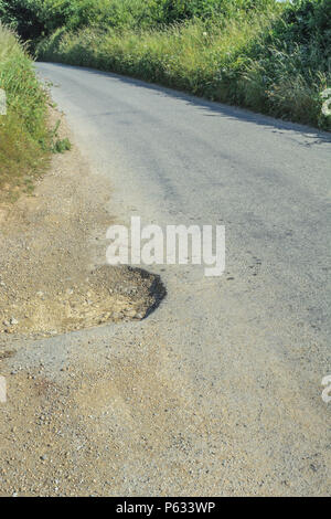 Pothole at the edge of a quiet tarmac country road. Car pothole breakdowns on the increase. - Stock Image