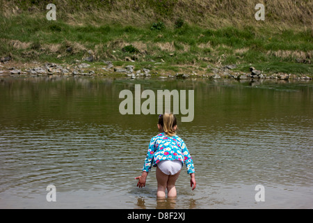 3 year old girl taking a paddle at the seaside. - Stock Image