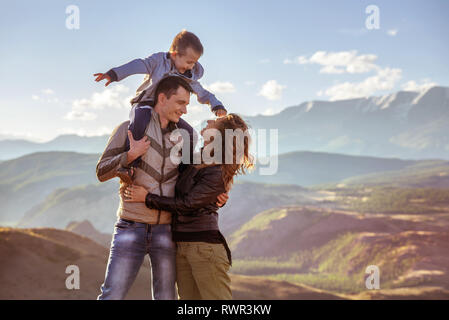 Happy family with young son stands against mountains - Stock Image