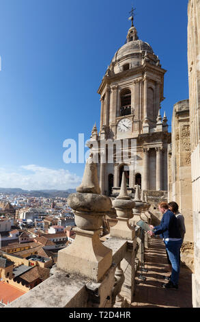 A couple looking at the view of Malaga Old town from the roof of Malaga Cathedral, on a roof tour,  Malaga Andalusia Spain - Stock Image