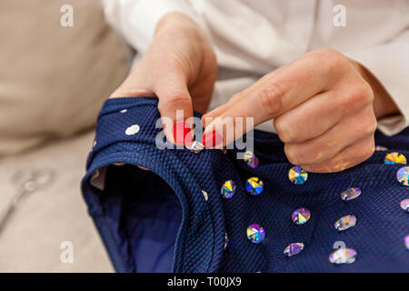 Girl designer hands with a red manicure sew rhinestones to the blue swimsuit - Stock Image