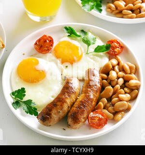 Dish for breakfast with fried sausages, eggs, beans, tomatoes, greens on plate over white stone background - Stock Image