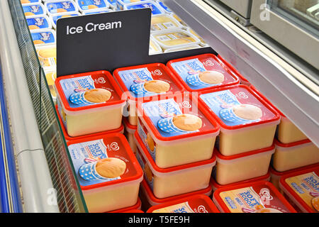 Close up of top of tub Walls brand soft scoop vanilla light ice cream tubs in stack in frozen food cabinets self service supermarket aisle England UK - Stock Image