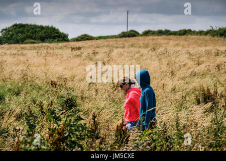 Two young women in hoodies walking in fields at Bempton Cliffs RSPB Reserve, UK. One woman has her hood up hoody hoodie. - Stock Image