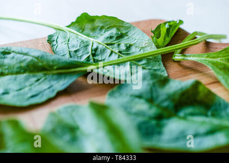 Fresh Baby Spinach Leaves on Wooden Board. Organic Food. - Stock Image