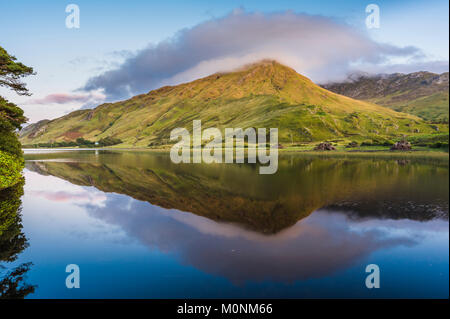 Kylemore Lough, Connemara, Co Galway is almost perfectly still just after sunset with a perfect reflection - Stock Image
