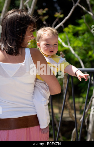 Mother holding toddler tourists in Mijas Pueblo, Costa del Sol, Andalucia, Spain - Stock Image