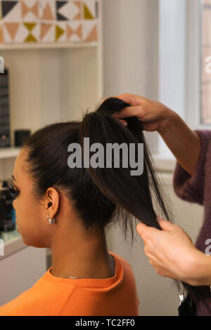 Hands professional female hairdresser doing evening hairstyle for her client. Hairdressing services. Сreating hairstyle. Hair styling process. Beauty  - Stock Image