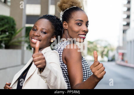 Two happy young businesswomen stand back to back to make sign of appreciation - Stock Image