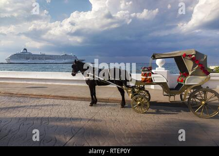 Horse Carriage and Large Cruise Ship Liner against the background of dramatic stormy sky in port of Cozumel, Mexico - Stock Image