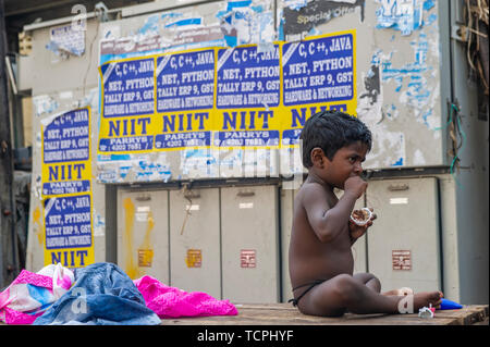 Poverty in Chennai, India, where a young Indian child eats in a run down area - Stock Image